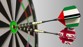 Flags of the UAE and the United Kingdom on darts hitting bullseye of the target. International cooperation or. Competition animation stock video footage