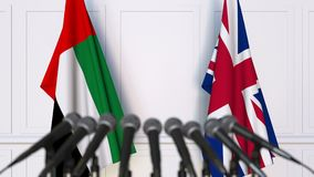 Flags of the UAE and The United Kingdom at international meeting or negotiations press conference. 3D animation stock video footage