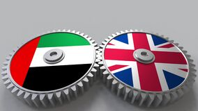 Flags of the UAE and the United Kingdom on meshing gears. International cooperation conceptual animation. Flags of the UAE and the United Kingdom on meshing stock video footage