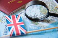 Flags of UK, magnifying glass, passport on a map. Tourism concept.  stock photography