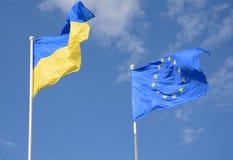 Flags of Ukraine and European Union EU against the blue sky. Flags of Ukraine and European Union EU against the blue sky Royalty Free Stock Image
