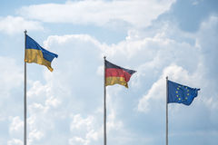 Flags of Ukraine, Germany and the European Union flutter on wind Stock Images