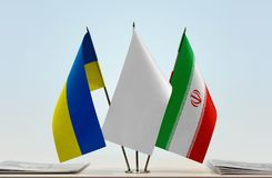 Flags of Ukraine and Iran. Desktop flags of Ukraine and Iran with white flag between stock image