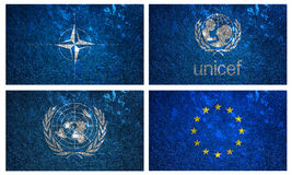 Flags of UNICEF, NATO, United Nation and EURO. On wall texture Stock Images