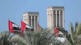 Flags of the United Arab Emirates. Traditional Wind Towers in the background. Middle East stock video footage