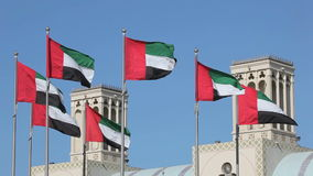 Flags of the United Arab Emirates. Traditional Wind Towers in the background. Middle East stock video