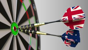 Flags of the United Kingdom and Australia on darts hitting bullseye of the target. International cooperation or. Competition animation stock video footage