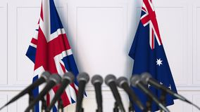 Flags of the United Kingdom and Australia at international meeting or negotiations press conference. 3D animation stock video