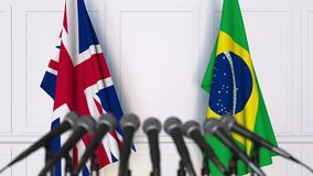 Flags of the United Kingdom and Brazil at international meeting or negotiations press conference. 3D animation stock video footage