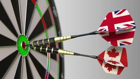 Flags of the United Kingdom and Canada on darts hitting bullseye of the target. International cooperation or competition. Animation stock footage
