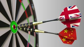 Flags of the United Kingdom and China on darts hitting bullseye of the target. International cooperation or competition. Animation stock video