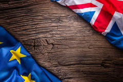 Flags of United kingdom and european union on rustic oak board. UK and USA flags together diagonally.  Royalty Free Stock Photo