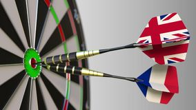 Flags of the United Kingdom and France on darts hitting bullseye of the target. International cooperation or competition. Animation stock video footage