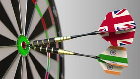Flags of the United Kingdom and India on darts hitting bullseye of the target. International cooperation or competition. Animation stock video