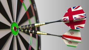 Flags of the United Kingdom and Iran on darts hitting bullseye of the target. International cooperation or competition. Animation stock video