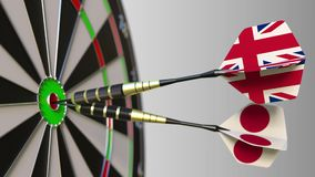 Flags of the United Kingdom and Japan on darts hitting bullseye of the target. International cooperation or competition. Animation stock video