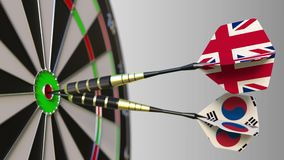Flags of the United Kingdom and Korea on darts hitting bullseye of the target. International cooperation or competition. Animation stock footage