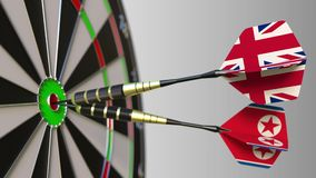 Flags of the United Kingdom and North Korea on darts hitting bullseye of the target. International cooperation or. Competition animation stock footage