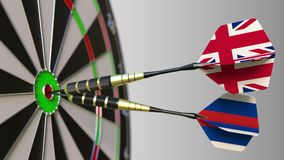 Flags of the United Kingdom and Russia on darts hitting bullseye of the target. International cooperation or competition. Animation stock footage