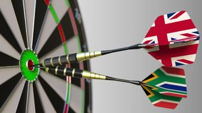 Flags of the United Kingdom and South Africa on darts hitting bullseye of the target. International cooperation or. Competition Stock Photography