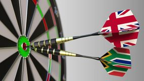 Flags of the United Kingdom and South Africa on darts hitting bullseye of the target. International cooperation or. Competition animation stock video footage