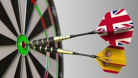 Flags of the United Kingdom and Spain on darts hitting bullseye of the target. International cooperation or competition. Animation stock footage