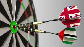 Flags of the United Kingdom and the UAE on darts hitting bullseye of the target. International cooperation or. Competition animation stock footage