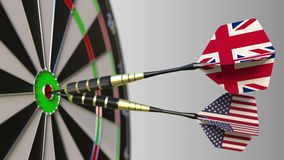 Flags of the United Kingdom and the USA on darts hitting bullseye of the target. International cooperation or. Competition animation stock video