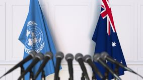 Flags of the United Nations and Australia at international meeting or negotiations press conference. 3D animation stock video