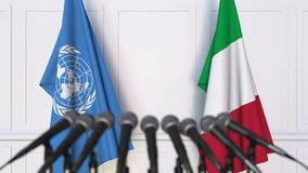 Flags of the United Nations and Italy at international meeting or negotiations press conference. 3D animation stock footage
