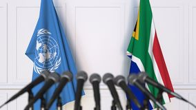 Flags of the United Nations and South Africa at international meeting or negotiations press conference. 3D animation stock video footage