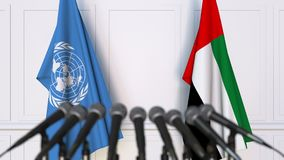 Flags of the United Nations and the UAE at international meeting or negotiations press conference. 3D animation stock video footage