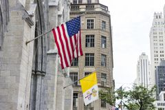 Flags of the United States of America and the Vatican State. New York City. Flags of the United States of America and the Vatican City State hanging from the stock image