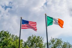 Flags of United states and Irland fluttering against blue sky, near Rhode Island irish famine memorial, Providence, USA. Flags of United states and Irland stock photos