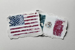Flags of United States and Mexico. The flag of United States and the flag of Mexico in two aged pieces of paper on an off-white background Royalty Free Stock Image