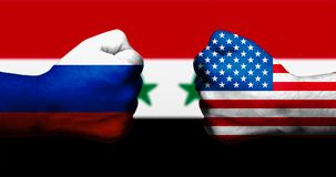 Flags of the United States and Russia painted on two clenched fists facing each other on background of blurred flag of Syria/conce. Pt of complex civil war in Royalty Free Stock Photo