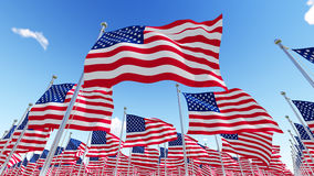 Flags of USA against blue sky. Royalty Free Stock Images