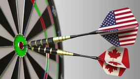 Flags of the USA and Canada on darts hitting bullseye of the target. International cooperation or competition conceptual. Flags of the USA and Canada on darts stock photo