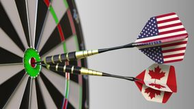 Flags of the USA and Canada on darts hitting bullseye of the target. International cooperation or competition conceptual. Flags of the USA and Canada on darts stock video footage