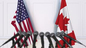 Flags of the USA and Canada at international meeting or negotiations press conference. 3D animation stock footage