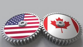Flags of the USA and Canada on meshing gears. International cooperation conceptual animation. Flags of the USA and Canada on meshing gears. International stock video