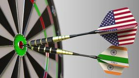 Flags of the USA and India on darts hitting bullseye of the target. International cooperation or competition conceptual. Flags of the USA and India on darts Royalty Free Stock Image
