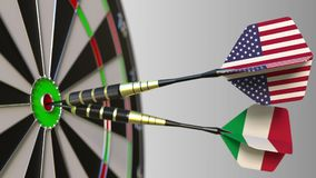 Flags of the USA and Italy on darts hitting bullseye of the target. International cooperation or competition conceptual Stock Photo