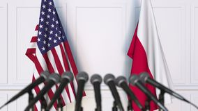 Flags of the USA and Poland at international meeting or negotiations press conference. 3D animation stock footage