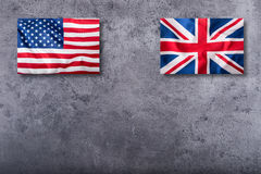 Flags of the USA and the UK. Union Jack flag on concrete background.  stock image