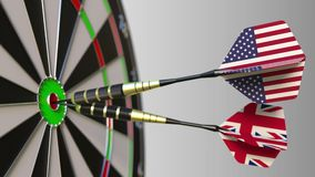 Flags of the USA and the United Kingdom on darts hitting bullseye of the target. International cooperation or. Competition animation stock video