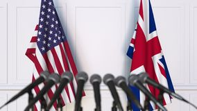 Flags of the USA and The United Kingdom at international meeting or negotiations press conference. 3D animation stock footage