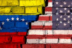 Flags of USA and Venezuela on the brick wall with big crack in the middle. Symbol of problems between countries royalty free stock photo