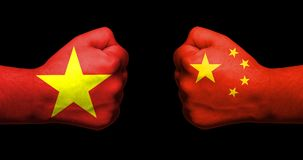 Flags of Vietnam and China painted on two clenched fists facing royalty free stock photography