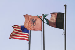Flags of war. American flag along side the Afghani flags symbolic of war and peace in a world full of military conflict and war on terror and terrorists still Royalty Free Stock Images